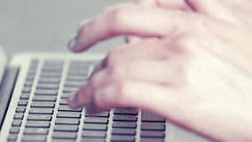 Woman's hands typing on a laptop computer. Tilt down shot of a woman's hands typing fast on a laptop computer stock footage