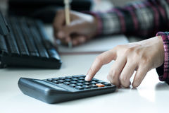 Woman`s hands using calculator on table Royalty Free Stock Images