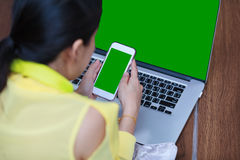 Woman`s hands using cell phone and laptop computer on floor wood. Back view of woman`s hands using smart phone and laptop computer on floor wooden. Green screen Royalty Free Stock Photography