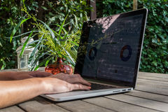 Woman`s hands using laptop with analytical graph on desk in the garden, work on fresh air Stock Photos