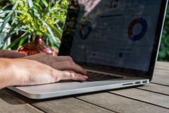 Woman`s hands using laptop with analytical graph on desk in the garden, work on fresh air Royalty Free Stock Photography