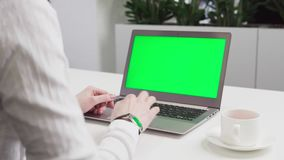 Woman`s hands using laptop with green screen on table. Woman`s hands in white shirt using laptop with green screen on table stock video