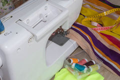 Woman`s hands using sewing machine with reels of colour threads Royalty Free Stock Image