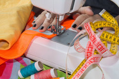 Woman`s hands using sewing machine with reels of colour threads Royalty Free Stock Photo