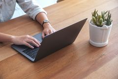 Woman`s hands using and typing on laptop keyboard on the table stock photos