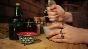 Woman`s hands vigorously grind, stir and crush ingredients in mortar and pestle