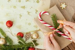 Woman s hands wrapping Christmas gift, close up. Unprepared christmas presents on wooden background with decor elements and items