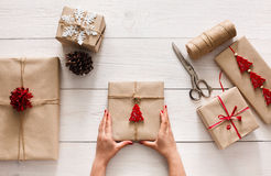 Woman's hands wrapping christmas holiday present with craft twine. Creative hobby. Woman's hands show christmas holiday handmade present in craft paper with Stock Photography