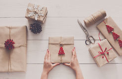 Woman`s hands wrapping christmas holiday present with craft twine. Creative hobby. Woman`s hands show christmas holiday handmade present in craft paper with Royalty Free Stock Photos