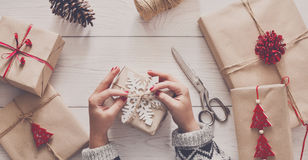 Woman`s hands wrapping christmas holiday present with craft twine. Creative hobby. Woman`s hands wrap christmas holiday handmade present in craft paper with Stock Images