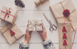 Woman`s hands wrapping christmas holiday present with craft twine. Creative hobby. Woman`s hands wrap christmas holiday handmade present in craft paper with Stock Photography