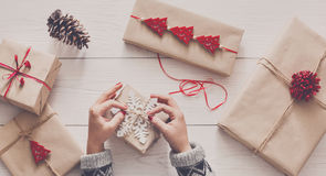 Woman`s hands wrapping christmas holiday present with craft twine. Creative hobby. Woman`s hands wrap christmas holiday handmade present in craft paper with Stock Photo
