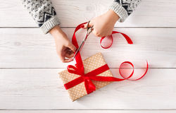 Woman's hands wrapping christmas holiday present iwith red ribbon Royalty Free Stock Photos