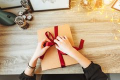 Woman wrapping present in paper with red ribbon. stock photos