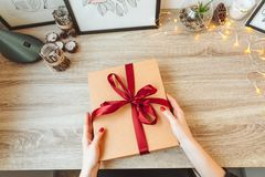 Woman wrapping present in paper with red ribbon. royalty free stock images