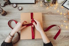 Woman wrapping present in paper with red ribbon. royalty free stock photography