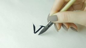 Woman`s hands writing Chinese hieroglyph. Female hand holding a writing brush calligraphy Chinese characters, close up.  Stock Image