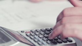 Woman's hands writing with a pencil and typing on a calculator stock video footage