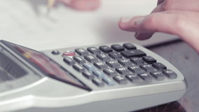 Woman's hands writing with a pencil and typing on a calculator stock video