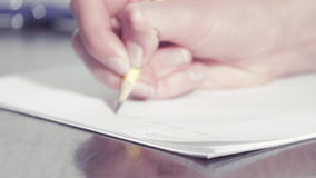 Woman's hands writing with a pencil stock footage