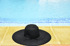 Woman's hat at the feet of the pool Stock Photos