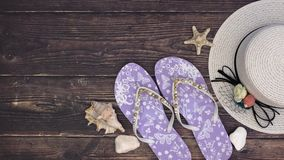 Woman`s hat slippers and sea shells on the wooden background - Stop motion stock video