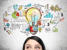 Woman's head and colorful startup planning sketch. Close up of woman's head against concrete wall with giant light bulb and colorful startup sketch royalty free stock photos