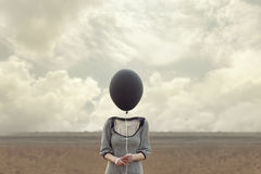Woman`s head replaced by a black balloon. In a surreal place stock photography