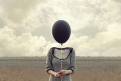 Woman`s head replaced by a black balloon. In a surreal place royalty free stock photo