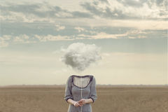 Woman`s head Replaced by a soft cloud in a surreal situation. Woman`s head Replaced by a soft cloud royalty free stock photography