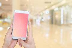 Woman's and holding smart phone with blur shopping mall backgrou Royalty Free Stock Image