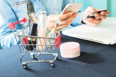Woman`s items and cosmetics in shopping cart. Woman`s hands using mobile phone, laptop and credit card, Beauty online shopping concept royalty free stock photography