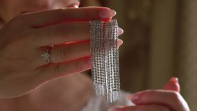 Woman`s jewelry earrings. Waving slowmotion. Bride put on stock footage