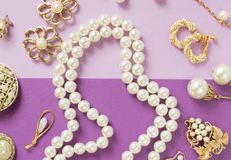 Woman`s Jewelry. Vintage jewelry background. Beautiful gold tone and pearls brooches, braceletes, necklaces and earrings on purpl. E background. Flat lay, top stock images