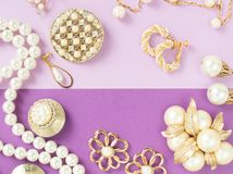 Woman`s Jewelry. Vintage jewelry background. Beautiful gold tone and pearls brooches, braceletes, necklaces and earrings on purpl. E background. Flat lay, top stock photos