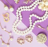 Woman`s Jewelry. Vintage jewelry background. Beautiful gold tone and pearls brooches, braceletes, necklaces and earrings on purpl. E background. Flat lay, top stock photo