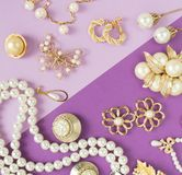 Woman`s Jewelry. Vintage jewelry background. Beautiful gold tone and pearls brooches, braceletes, necklaces and earrings on purpl. E background. Flat lay, top royalty free stock photos