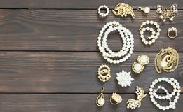 Woman`s Jewelry. Vintage jewelry background. Beautiful pearl brooches, braceletes, necklaces and earrings on wood background. Fla Stock Photo