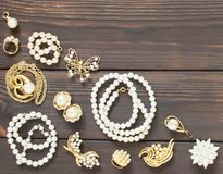 Woman`s Jewelry. Vintage jewelry background. Beautiful pearl brooches, braceletes, necklaces and earrings on wood background. Fla Royalty Free Stock Photo