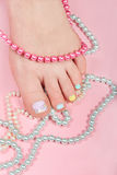 Woman's leg with beautiful pedicure and colorful necklaces Stock Images