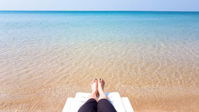 Woman`s leg lay on the white armchair on the beach Royalty Free Stock Photography