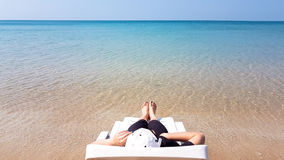 Woman`s leg lay on the white armchair on the beach Stock Photos