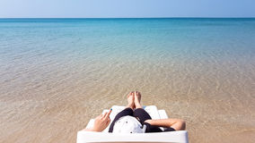 Woman`s leg lay on the white armchair on the beach Royalty Free Stock Photos