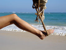 Woman's Leg in Paradise. Woman's Leg in in Rope swing on the beach, obviously in a tropical setting... very sexy and invigorating Royalty Free Stock Photos