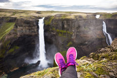 Woman's leg relax on cliff near fantastic waterfall Stock Photo