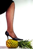 Woman's leg wearing heals and stocking standing on a pineapple. Attractive female's leg standing on a pineapple tilted over on its side Royalty Free Stock Photography