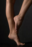 Woman's legs. Pair of female feet on a dark background Stock Photos