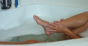 Woman washind legs stock video footage