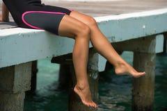 Woman's legs at beach jetty Royalty Free Stock Photo