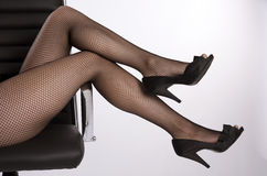 Woman's legs in black fishnet tights Royalty Free Stock Photos